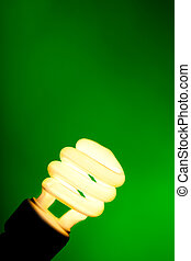 Compact flourescent light bulb on green background