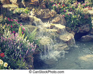 Waterfall with flowers in garden