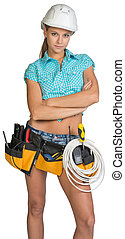 Serious electrician in helmet, shorts, shirt, tool belt with tools