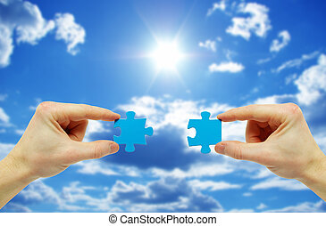 puzzle in hand isolated on sky background