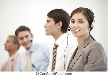Callcenter - four people sitting in a row with headset on