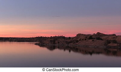 Beautiful Lake Sunset - a colorful sunset reflected in a...