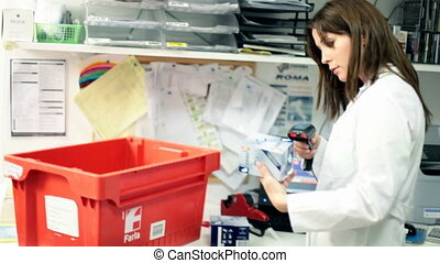 Pharmacist working in pharmarmacy - Woman pharmacist in...