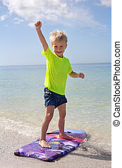 Happy Child Standing on Boogie Board in Ocean - A happy...