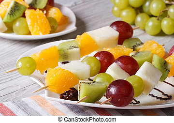Dessert of fresh fruit on skewers close-up. Horizontal -...