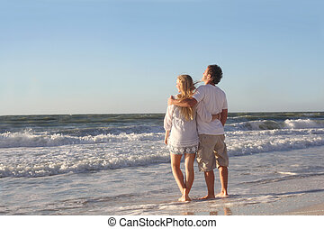Happy Couple Looking out Over Ocean While Walking on Beach -...