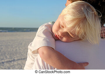 Young Child Sleeping in Father's Arms on Beach - A young...