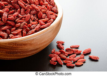 Wooden Bowl Full of Dried Goji Berries on the Dark Table...