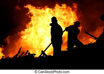Firefighters - Firemen fighting a raging fire with huge...