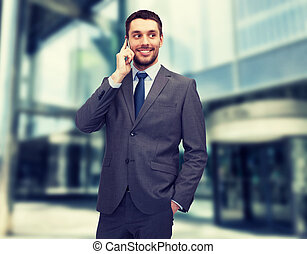 young smiling businessman with smartphone - business,...