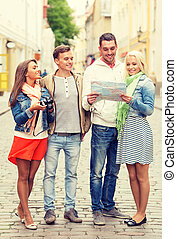 group of smiling friends with map and photocamera - travel,...
