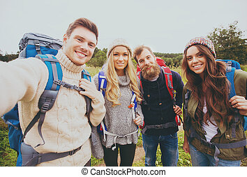 group of smiling friends with backpacks hiking - adventure,...