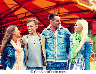 group of smiling friends in amusement park - leisure,...