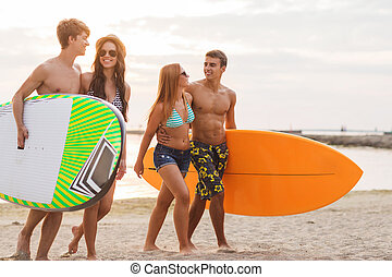 smiling friends in sunglasses with surfs on beach -...