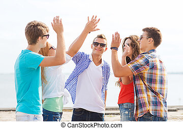 group of smiling friends making high five outdoors -...