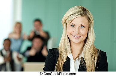 Businesswoman in front of her team in an office with a green...