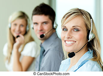 Young businesspeople smiling at the camera with headsets in...
