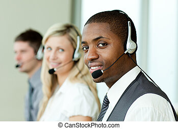 Businesspeople with headsets smiling at the camera