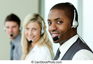 Businesspeople wearing headsets and smiling at work