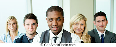 Business team in a row with ethnic manager in the center in...