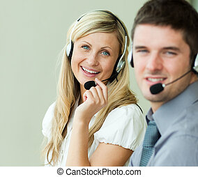 Two business people smiling at the camera with headsets at...