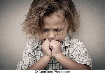 Portrait of sad little boy standing near the wall