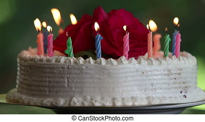 cake with burning candles and flowers