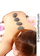 stone therapy - woman getting stone therapy at the health...
