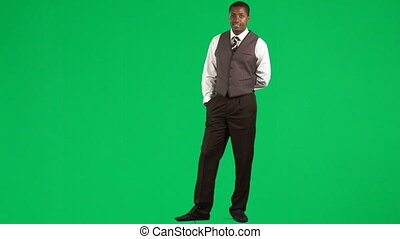 Ethnic businessman pointing next to him against green screen