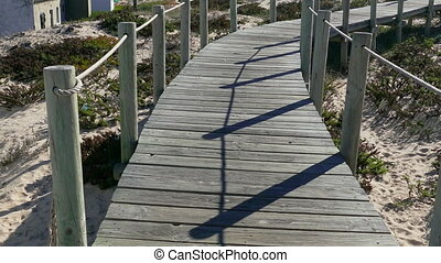 Walking on Wooden Footpath through Dunes Atlantic Ocean...