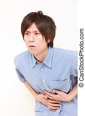 man suffers from stomachache - studio shot of young Japanese...