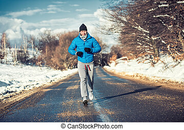 Muscular athlete man jogging outdoor on snow, training for...