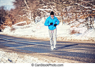 Athletic man jogging and training outdoor in park with snow...