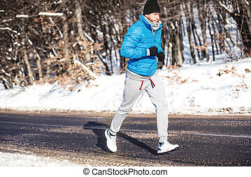 Young athlete going for a run outdoor in snow, hardcore...