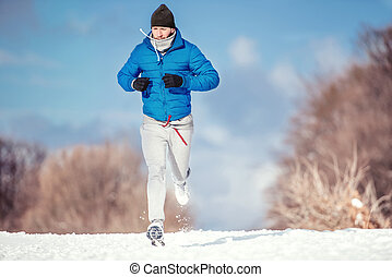 Fitness concept of a man running outdoor in snow on a cold...