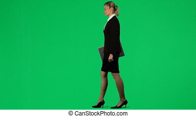 Businesswoman working with a laptop against green screen