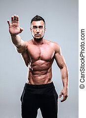 Handsome muscular man holding his palm out saying Stop or No...