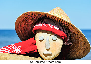 Wicker hat and bandana - Stone head with a wicker hat and...