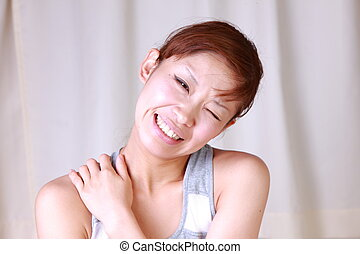 stiff neck - young Japanese woman suffers from stiff neck
