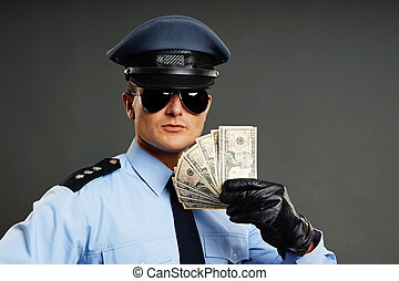 Policeman shows money - Policeman in uniform shows money on...