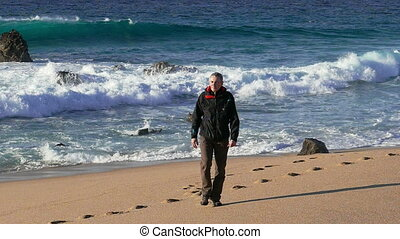 Man Walking on Beach with Waves in the Background