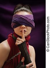 Blindfolded girl finger over lips violet blanket background
