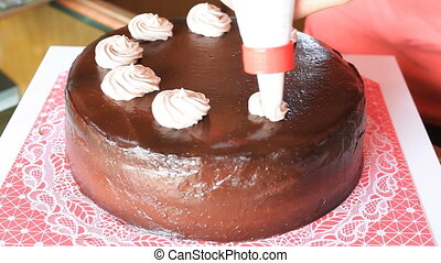 Step of whipped cream topping on chocolate cake