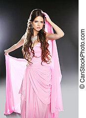 Beautiful young woman in pink chiffon dress. Makeup. Long wavy h