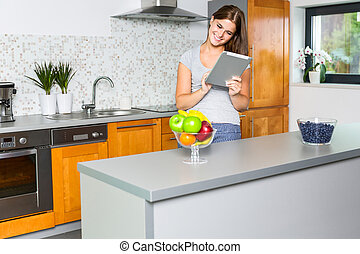 Smiling young woman surfing the net in the kitchen