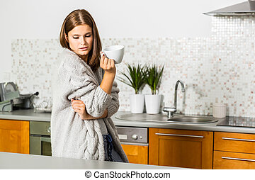 Young woman in cardigan with mug of hot tea