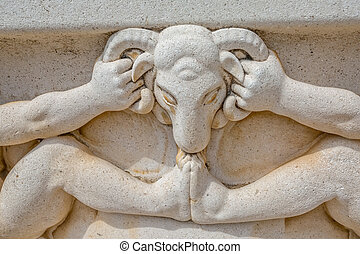 Stone well detail - Ram head carved in stone on the well at...