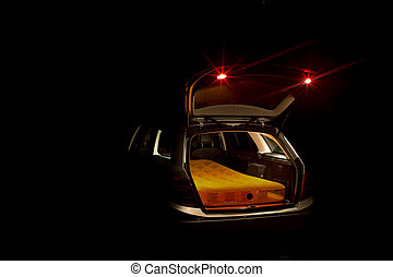 Open car boot with mattress - Night view of an illuminated...