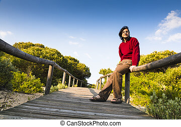 Man sitting on a coastal boardwalk - Man sitting on the...