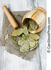 dried bay leaves and a wooden mortar on a light wooden...